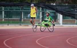 Young man in wheelchair and older man going round a track