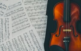 Scattered sheet music next to violin