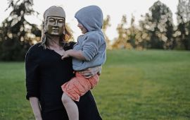 Woman wearing a mask holds child in her arms