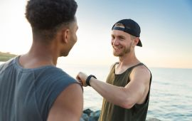 Two men at the beach check heart rate on watch